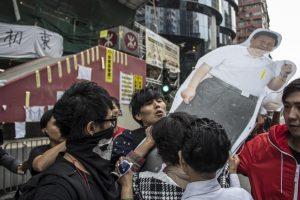 反佔領市民經常在佔領區與佔領人士發生衝突。圖為一名青年試圖阻截一名女士從旺角佔領區取去習近平的人形紙牌。
