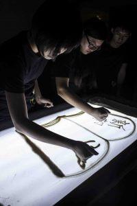手中沙成員示範「灑沙」-在燈箱上灑沙,用手指或指甲繪書或寫字。