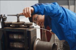 吳曉波拉住銀條的一端,仔細查看銀條通過機器。這是他打造銀飾的第一個步驟,嫻熟而細緻的動作一氣呵成。